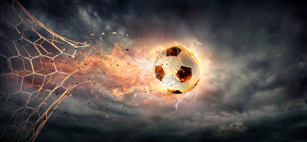 Fiery Soccer Ball breaking through The Net With Dramatic Sky stock photo