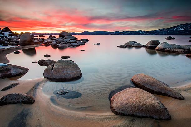 feurigen sonnenuntergang am lake tahoe - lake tahoe winter stock-fotos und bilder