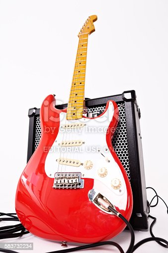 Cape Town, South Africa - July 2, 2016: A Stratocaster in the vintage Fender color Fiesta Red. This instrument is part of the Classic Vibe series manufactured in China by the Fender subsidiary Squier in 2013. The Classic Vibe guitars have been acclaimed by reviewers and guitarists around the world for their superior quality at comparatively affordable prices, although they are more expensive than other Squiers. This model reproduces vintage features of Fender Strats made in the 1950s. It is leaning against a Roland Cube 80GX amplifier and shot from a low angle distorting its shape..