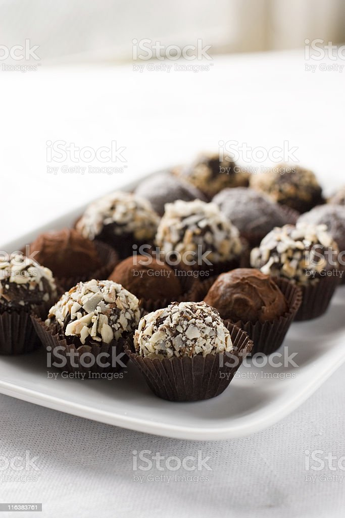 Fifteen chocolate Godiva truffles laid out on white plate royalty-free stock photo