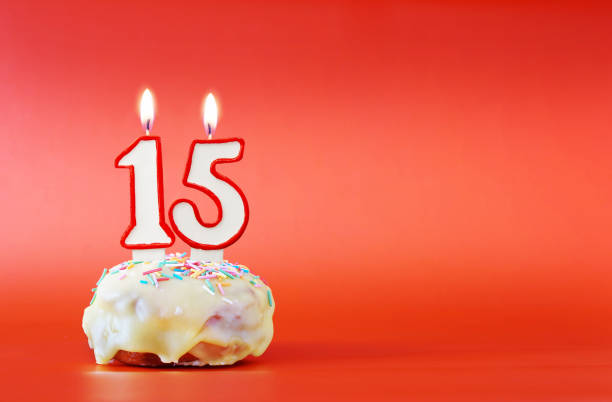 Fifteen years birthday. Cupcake with white burning candle in the form of number 15. Vivid red background with copy space stock photo