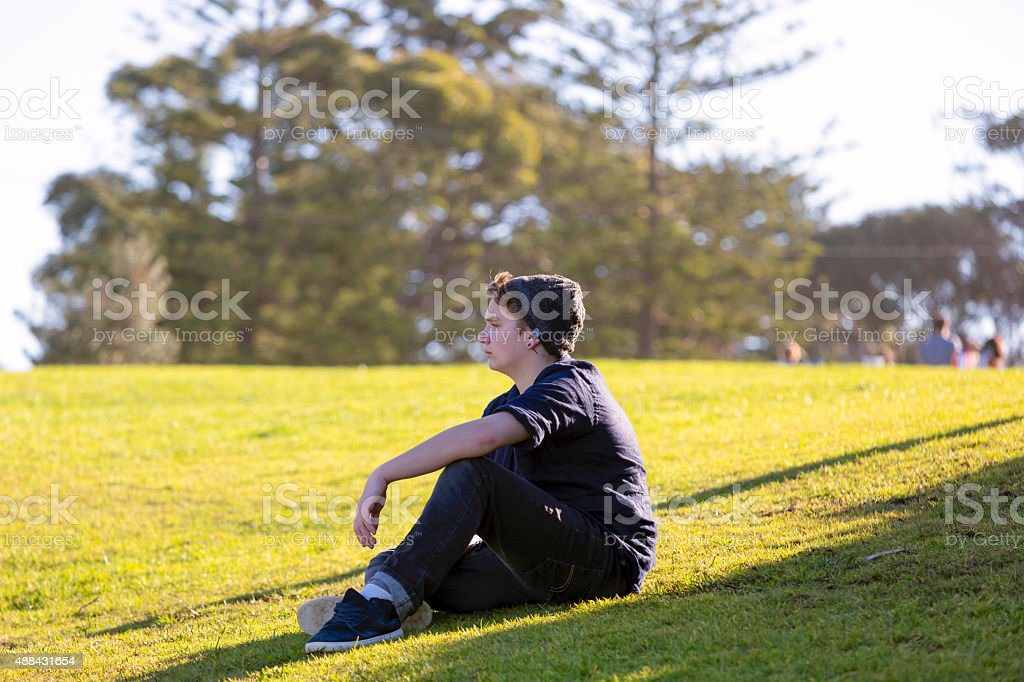 Fifteen years old teenage boy sitting on the grass​​​ foto