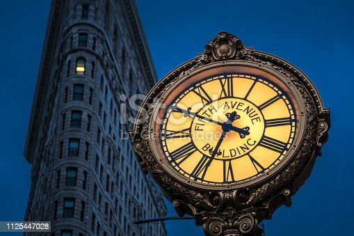 Low angle view of the Fifth Avenue Building Clock and the Flatiron Building at night.