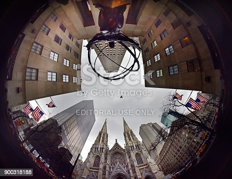 Fish-eye wide angle staring on 5th Avenue NYC looking up with St Patrick's Cathedral centre stage and the edge of the Rockefeller Centre and American flags. A single bird flies overhead