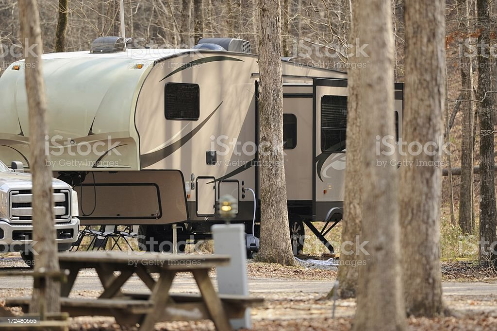Fifth wheel rv trailer in campsite with woods royalty-free stock photo