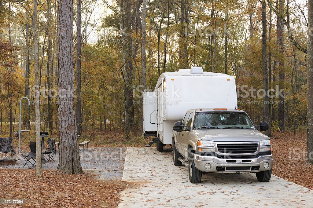 Fifth wheel travel trailer rv in wooded campsite during autumn royalty-free stock photo