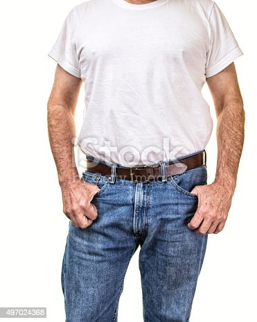 A cropped senior adult man is standing facing the camera in a confident pose with his hands near his hips and his thumbs hooked into the front pockets of his blue jeans. An old guy torso dressed in retro Fifties fashion style.
