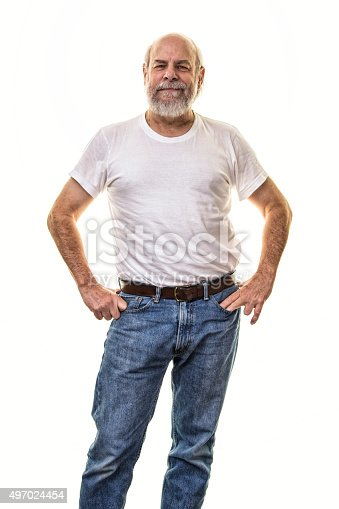 A relaxed, smiling 60-something grey beard senior adult man is standing facing the camera in a confident pose with his hands on his hips. He is wearing a white t-shirt and blue jeans. An old bald guy dressed in retro Fifties fashion style.