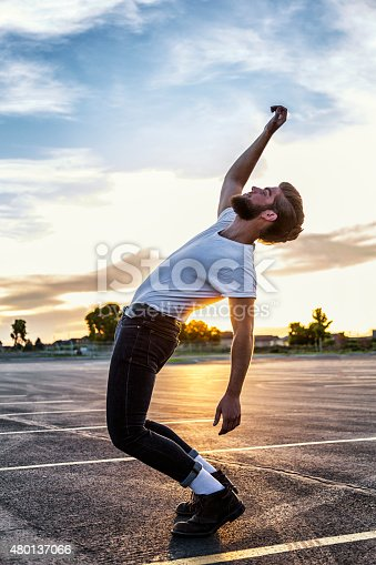 A 1950's Fifties greaser young man dressed in a white t-shirt, skin tight blue jeans and white socks is dancing alone on the high school parking lot. He is bending his legs, stretching his arms, and leaning over backwards while silhouetted in the late afternoon lens flare sunset.