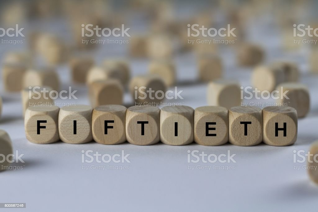 fiftieth - cube with letters, sign with wooden cubes stock photo