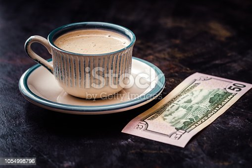 istock Fifty Dollar Banknote Next to a Coffee Cup on Table 1054998796