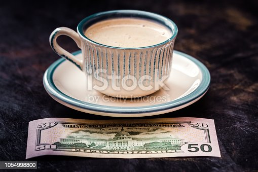istock Fifty Dollar Banknote Next to a Coffee Cup on Table 1054998800