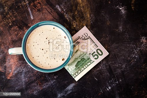 istock Fifty Dollar Banknote Next to a Coffee Cup on Table 1054998866