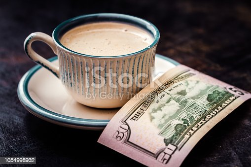 istock Fifty Dollar Banknote Next to a Coffee Cup on Table 1054998932