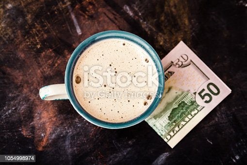 istock Fifty Dollar Banknote Next to a Coffee Cup on Table 1054998974