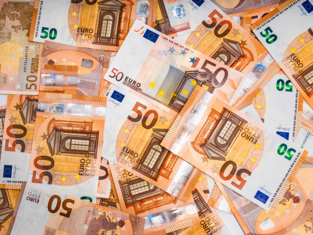 Fifty Euro bills piled up forming an abstract background Set of fifty euro bills scattered on a surface forming a nice abstract background fifty euro banknote stock pictures, royalty-free photos & images