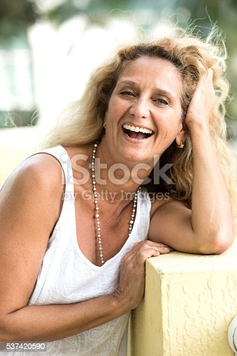 Fifty something woman smiling looking at the camera with her hands in her head