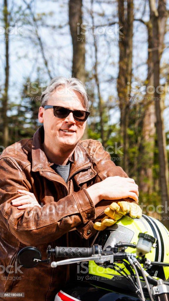 50 yaşındaki adam onun motosiklet üzerinde oturan ve kameraya gülümseyen stok fotoğrafı