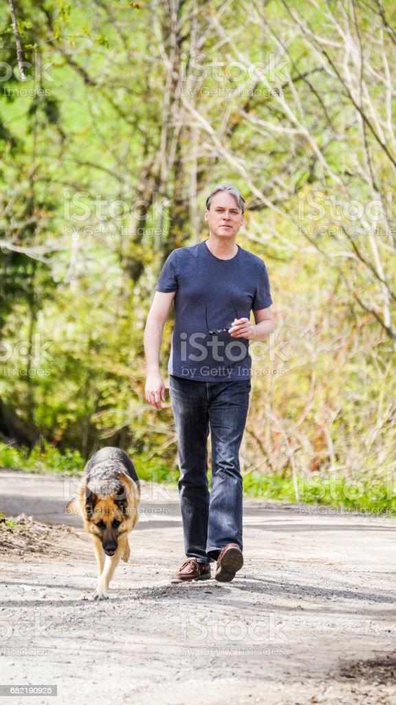 Elli yaşına bir driveway yürüme ve kameraya gülümseyen adam stok fotoğrafı