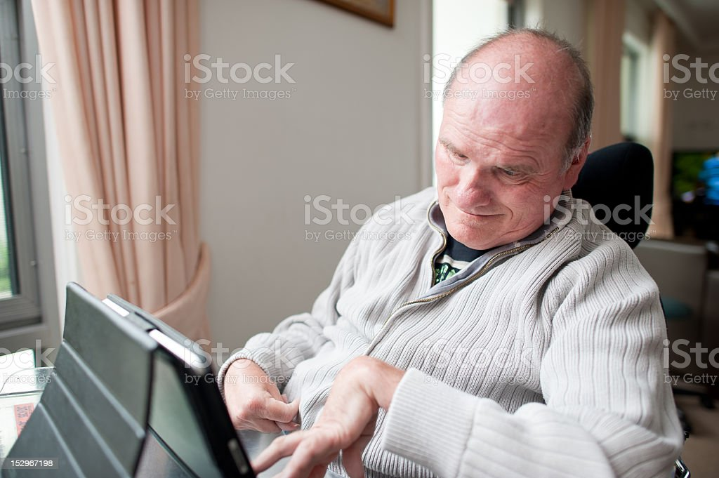 Fifty-five year old man with a disability using computer stock photo