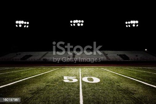 American football field at night under the stadium lights.
