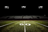 American football field at night under the stadium lights.