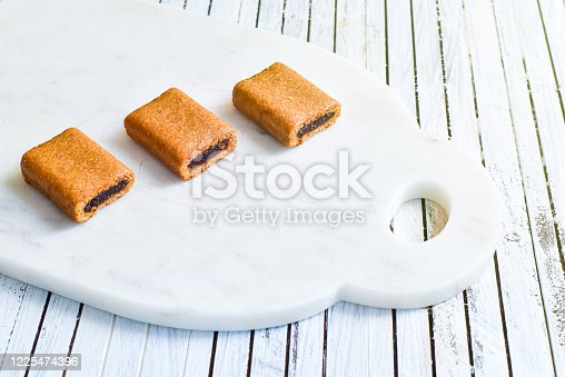 a collection of fig cookie bars on a wooden table