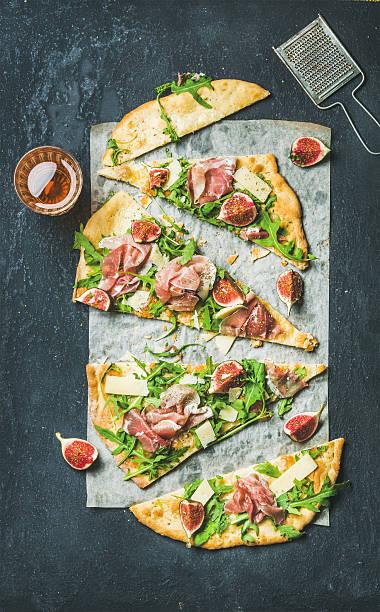 fig, prosciutto, arugula and sage flatbread pizza cut into pieces - fladenbrotpizza stock-fotos und bilder