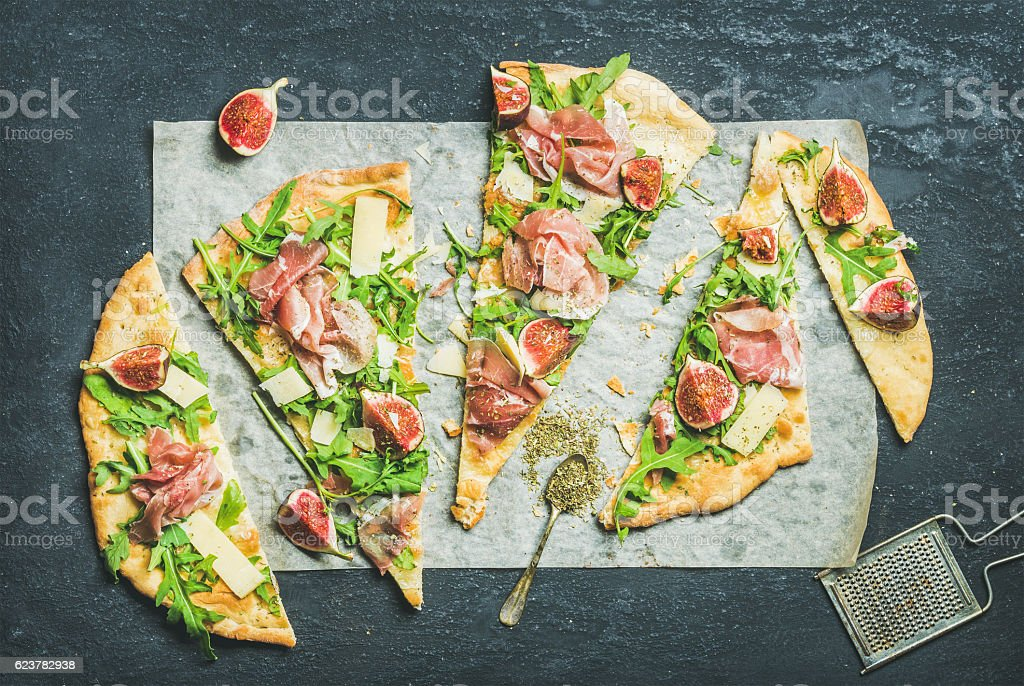 Fig, prosciutto, arugula and sage flatbread pizza on dark background stock photo