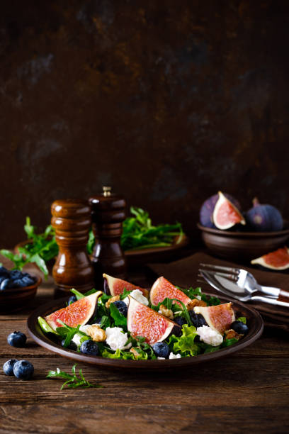 fig salad with goat cheese, blueberry, walnuts and arugula on wooden background. healthy food. lunch - fig salad imagens e fotografias de stock
