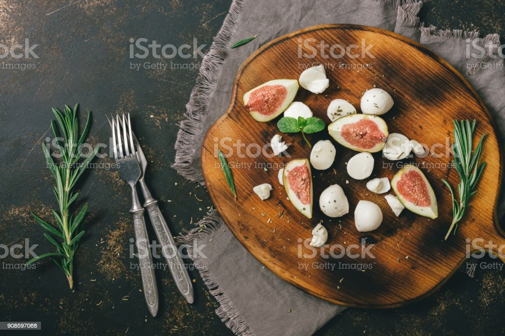 Fig with cheese on a cutting board, dark background. View from above. stock photo