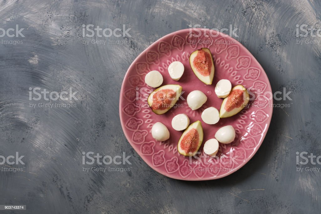 Fig with mozzarella cheese served on a pink plate, gray abstract background. Top view, copy space. stock photo