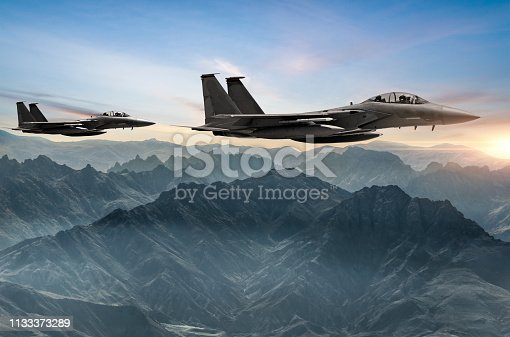 Figher jets flying over the fogy mountains at sunset