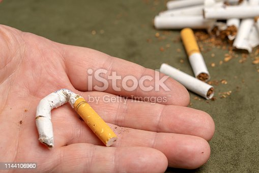 Fight against smoking. Broken cigarette on the palm.