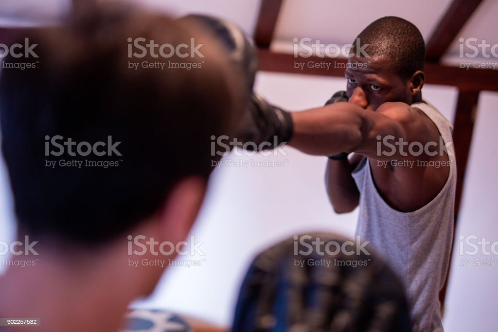 Young Handsome African Boxer Practicing Direct Punches With His Young...