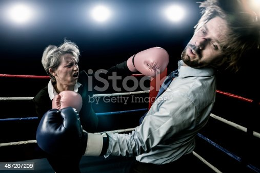 Businesswoman punching businessman in boxing fight