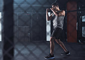Shot of a young man practicing his kickboxing routine at a gym