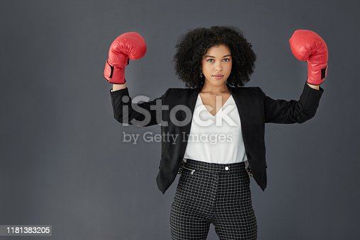 Studio portrait of a young corporate businesswoman posing wearing boxing gloves against a grey background