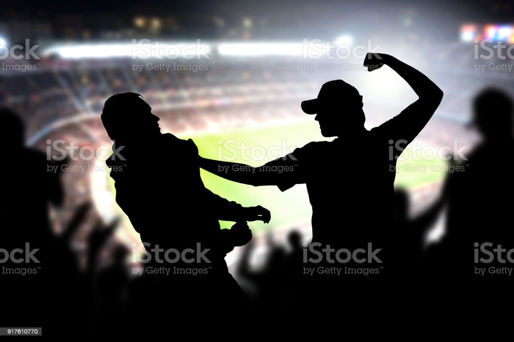 Fight in a football game crowd. Angry man hitting another spectator in soccer match audience. Violent argument between two fans of different teams and clubs. stock photo