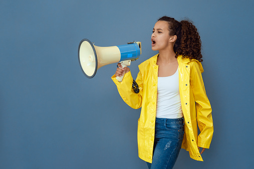 Beautiful teenager in yellow raincoat shouting in megaphone on blue background