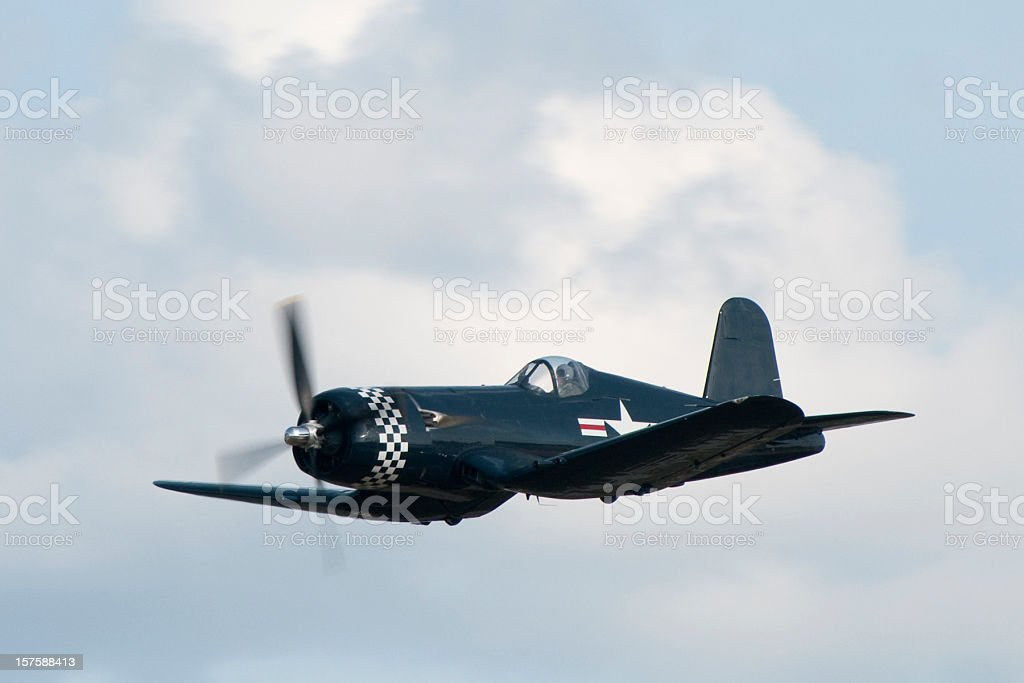 WWII fighter Corsair F4U airplane flying in cloudy sky royalty-free stock photo