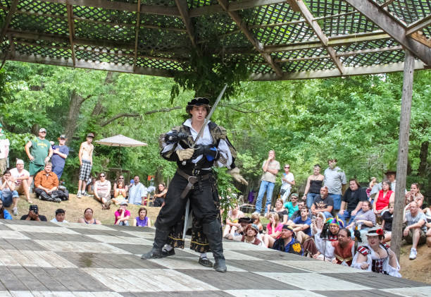 fighter in medieval costume looks amazed as woman fighter pins him with sword from behind and people watch renassiane festival - swashbuckler stock photos and pictures