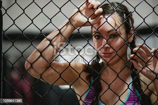 Portrait of a mid-adult MMA fighter leaning against the cage.