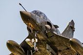 Close up view of a modern military armed fighter jet plane taking off.