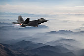 F-22 fighter jet flying over fogy  mountains at dusk