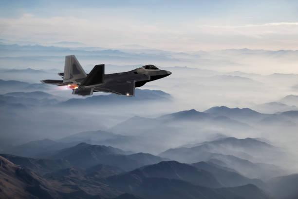 F-22-Kampfjet fliegt in der Dämmerung über neblige Berge – Foto