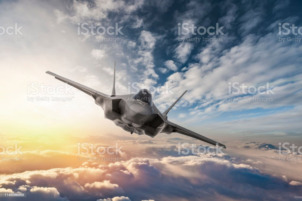 Fighter Jet flying over the clouds at sunset Fighter Jet flying over the clouds at sunset Advanced Tactical Fighter Stock Photo