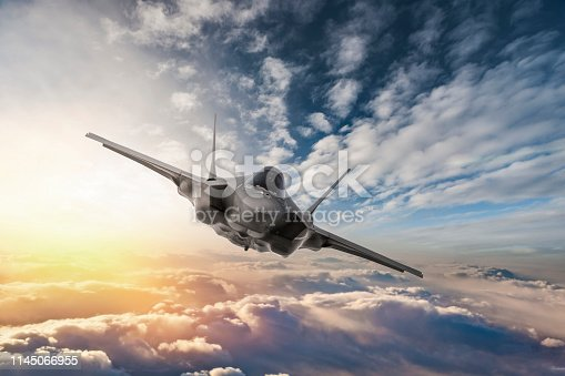 1145066973 istock photo Fighter Jet flying over the clouds at sunset 1145066955