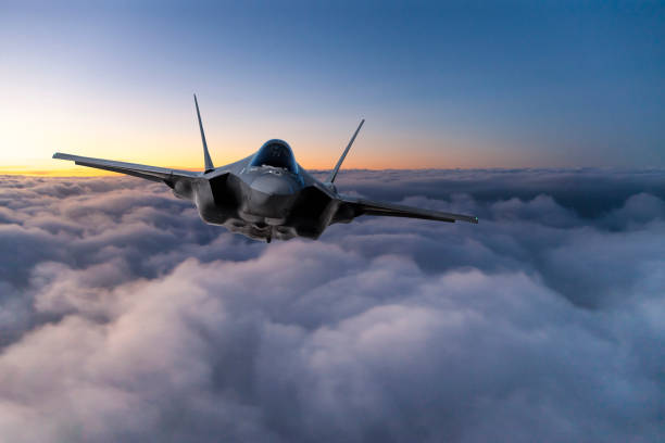 Fighter Jet flying over the clouds at sunset stock photo