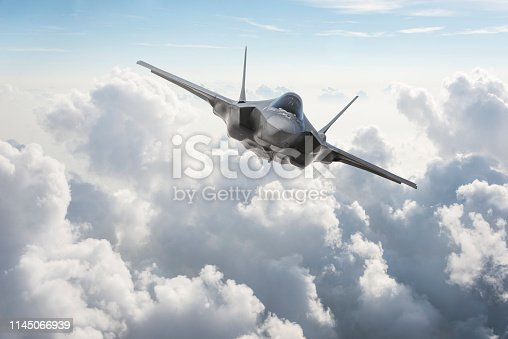 istock Fighter Jet flying over the clouds 1145066939
